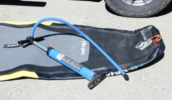 This photo shows a deflated stand-up paddle board with a manual air pump.