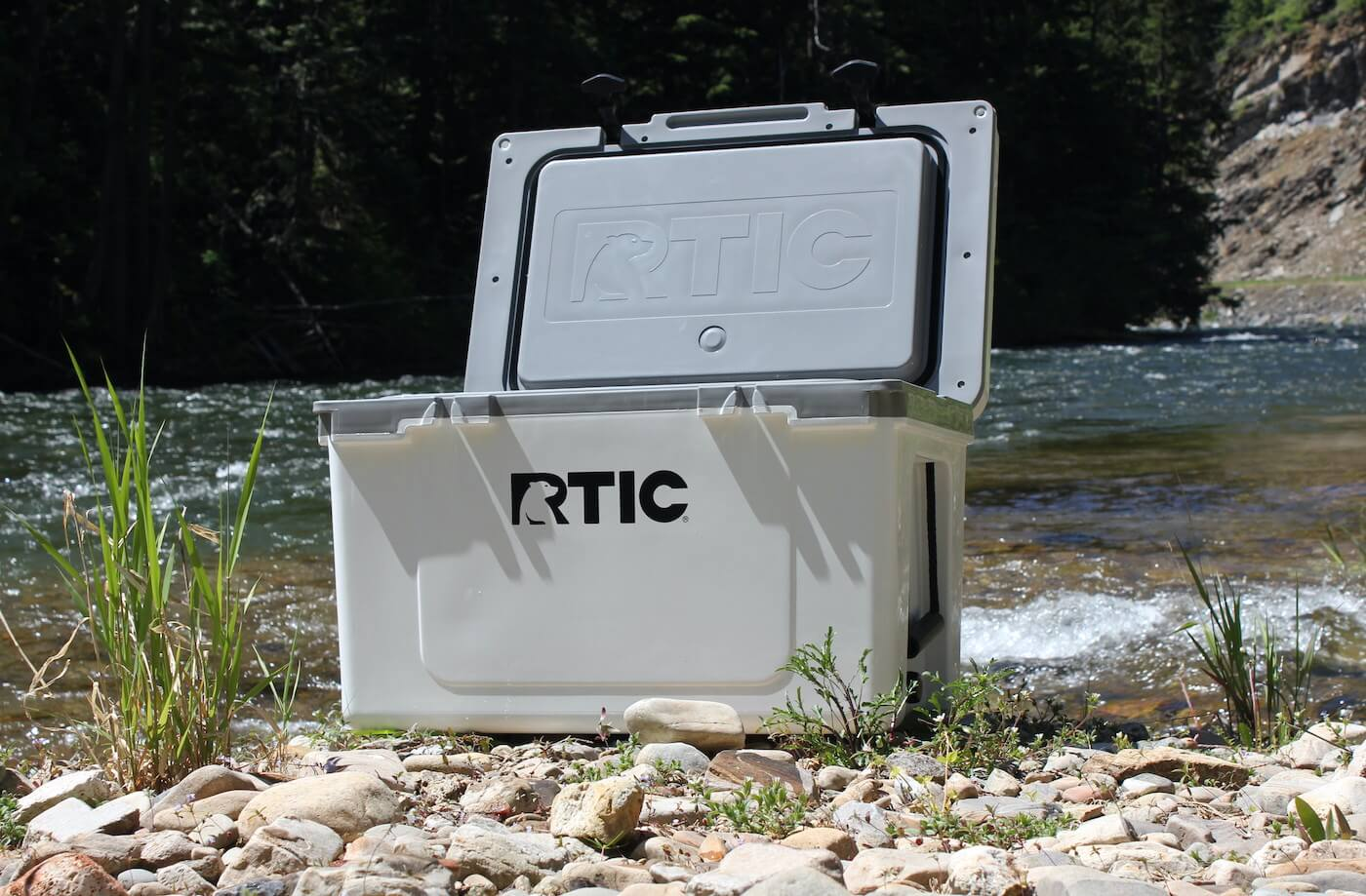 This review photo shows the RTIC Ultra-Light Cooler outside near a river just prior to the testing process by the author.