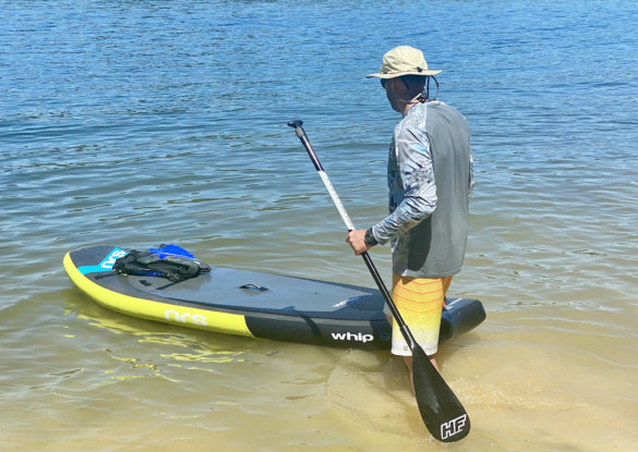 This photo shows the author testing the UA Iso-Chill Shorebreak Long Sleeve shirt with a SUP at the beach.