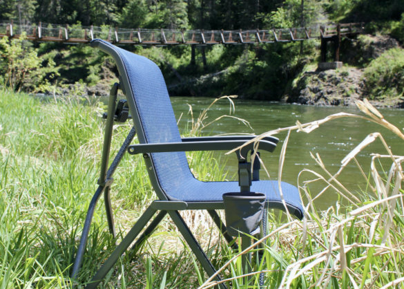 This photo shows a side view of the YETI Trailhead Camp Chair outside in the woods near a river.