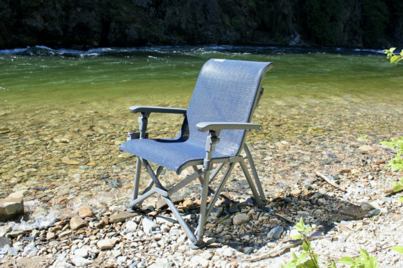 This review photo shows the YETI Trailhead Camp Chair setup outside near a river during the testing and review process.