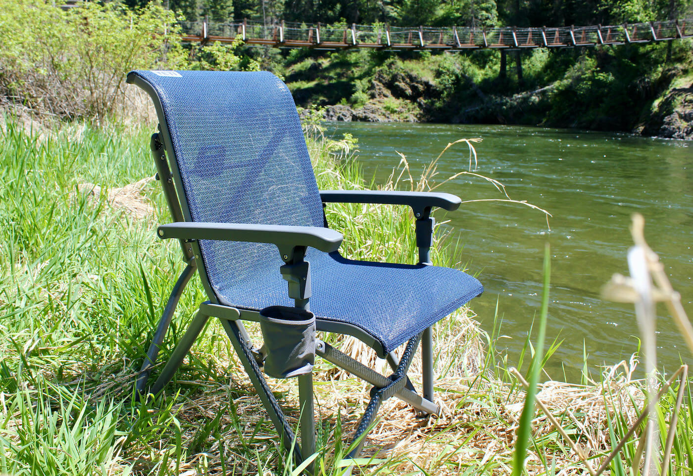 This review photo shows the YETI Trailhead Camp Chair near a river during the testing process by the author.
