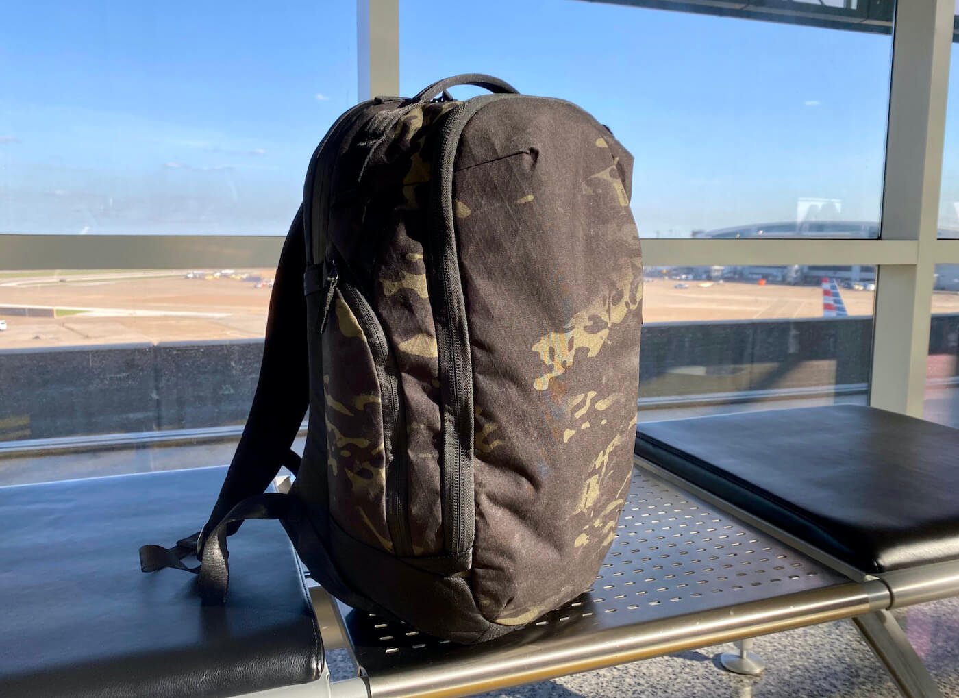 This review photo shows the Able Carry Max Backpack on a bench in an airport during the testing and review process.