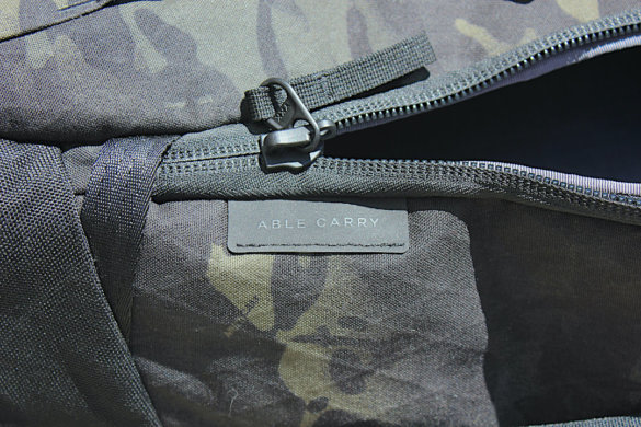 This photo shows the Able Carry brand tag on the Max Backpack.