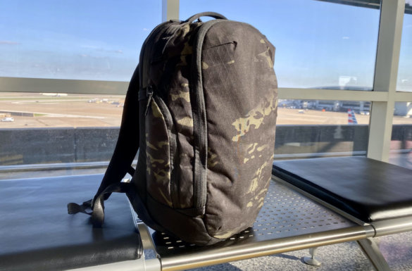 This review photo shows the Able Carry Max Backpack in the 'Dark Forest MCB' color option in an airport during the author's review process.
