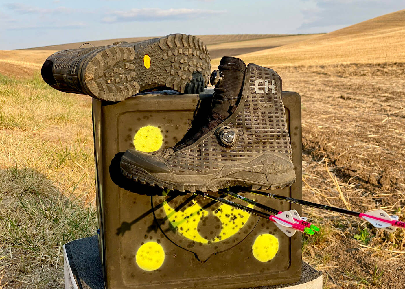 This review photo shows the Under Armour UA CH1 GORE-TEX Hunting Boots on an archery target out in a field.
