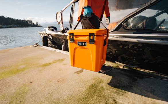 This photo shows a man with a King Crab Orange colored YETI Roadie 24 cooler on a dock near a boat.