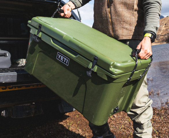 This closeup photo shows a man carrying a YETI Tundra 65 Hard Cooler in the Highland Olive color option.