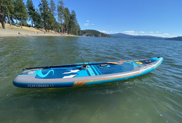 This review photo shows the Body Glove Performer 11 ISUP floating on a lake with the included paddle.
