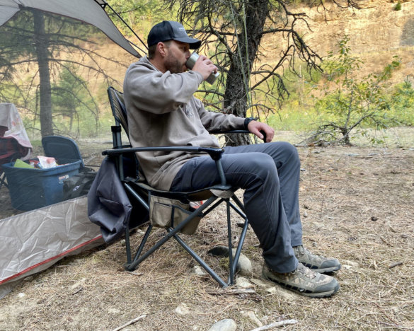 This photo shows the author sitting in the Cabela's Big Outdoorsman XL Fold-up Chair at a camping site during the testing and review process.