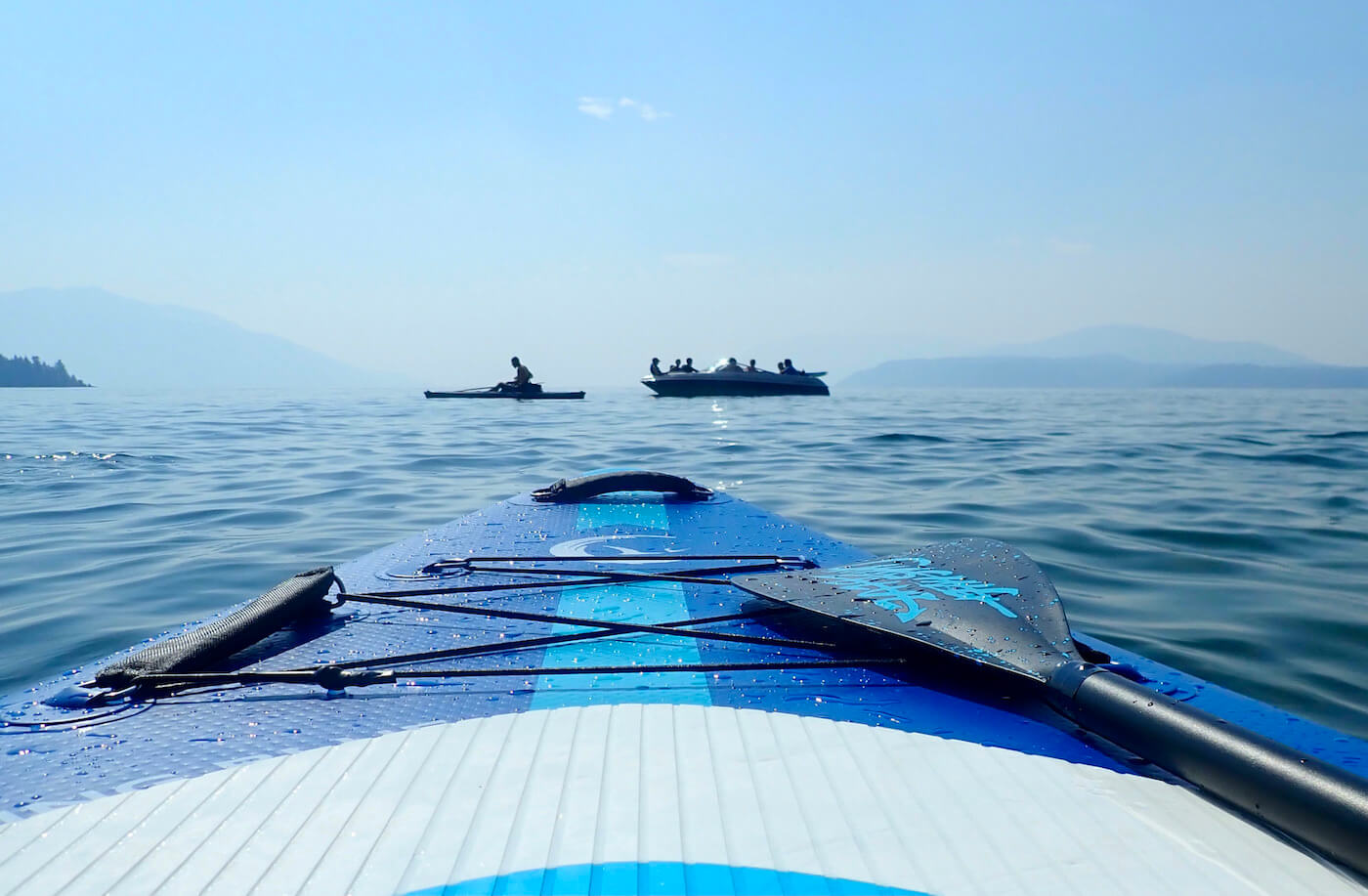 This review photo shows the Outdoor Master Infinite iSUP Chasing Blue paddle board on a lake during the testing process.