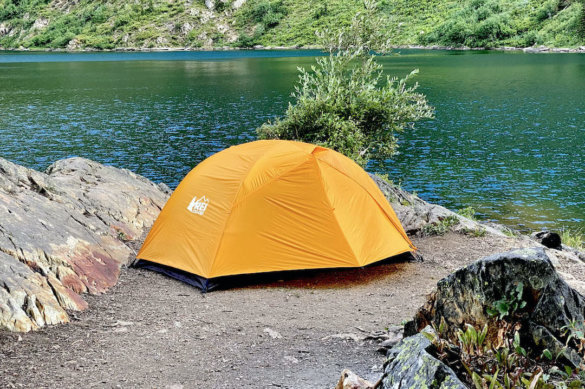 This review photo shows the REI Co-op Half Dome SL 2+ 2-person backpacking tent setup near a mountain lake.