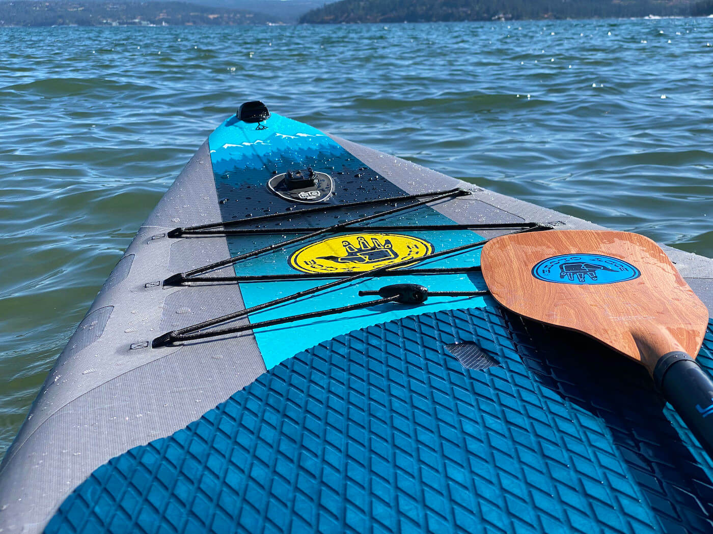 This review photo shows the Body Glove Performer 11 stand-up paddle board on a lake during the testing process.