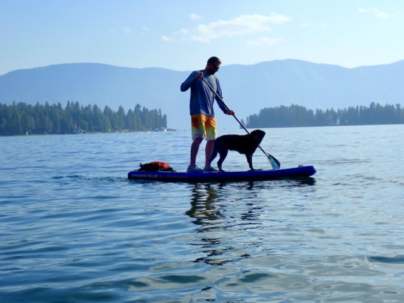 This review photo shows the author paddling the Outdoor Master Infinite iSUP Chasing Blue model on a lake during the testing and review process.