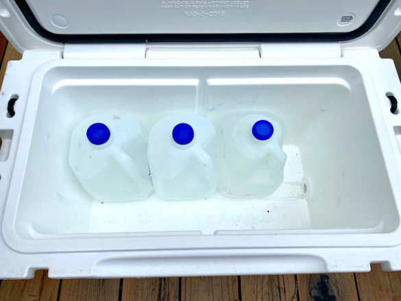This photo shows a typical 45-quart cooler with three gallon jugs inside to illustrate capacity considerations.