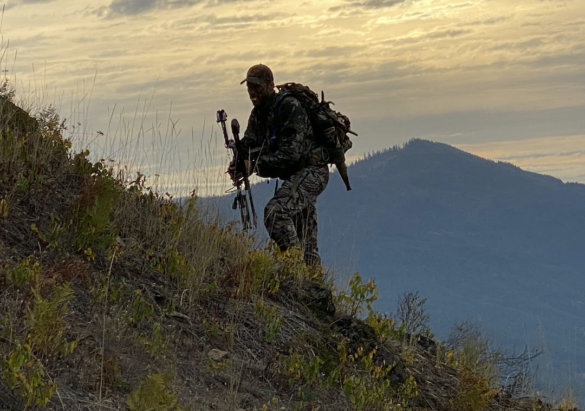 This photo shows the author climbing a mountain with a bow and hunting pack while testing the Ridge Reaper Raider HD hunting pants.