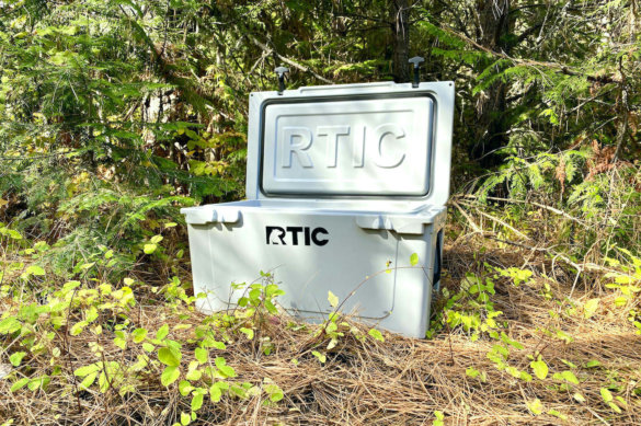 This testing and review photo shows the RTIC 65 QT Hard Cooler outside in a forest at a camping site.