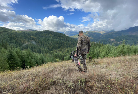 This photo shows a bow hunter wearing Under Armour hunting clothing while hunting in a forested mountain area.